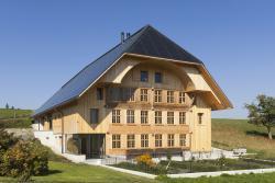 Frontansicht des vorbildlich sanierten DEFH Anliker, das dem traditionellen Baustil der ländlichen Umgebung von Affoltern i.E. trotz modernster Solartechnik treu bleibt.