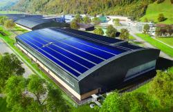 Ansicht des Pilatus Flugzeugwerke AG Industriebaus  von Süden. Die homogen dunkle PV-Anlage ist filigran in die Architektur der Halle integriert.